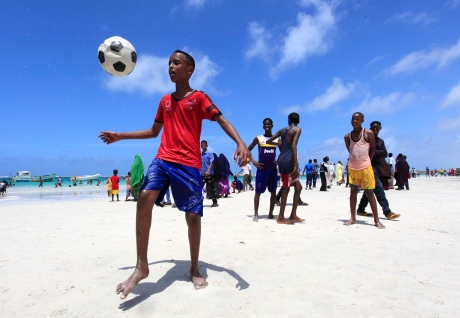 Somali boys play football in Lido beach while celebrating the Muslim Eid al-Fitr holiday, which marks the end of the fasting month of Ramadan, in capital Mogadishu August 8, 2013. REUTERS/Feisal Omar (SOMALIA - Tags: SOCIETY RELIGION SPORT SOCCER) - RTX12DXB